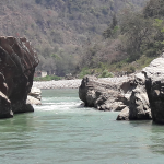 The Ganges River viewed from boulders on its bank.